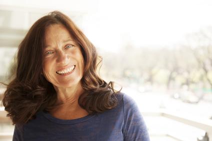 Happy mature woman using hyaluronic acid serum
