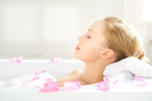girl relaxing in bathtub of rose water and rose petals